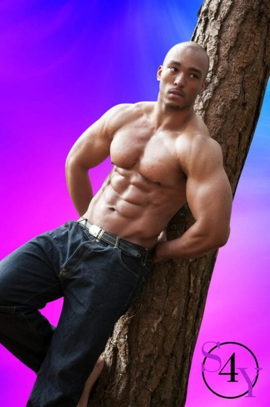 buff black exotic dancer leaning against a tree