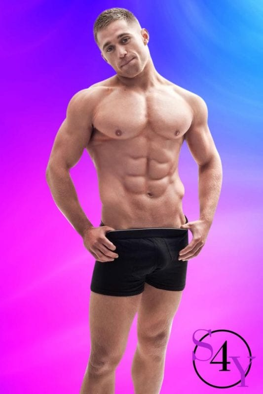 buff male dancer showing off abs in black shorts