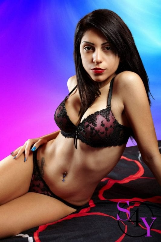 Latin woman in lingerie, sitting on the bed