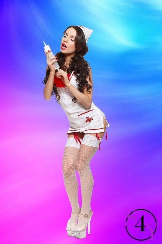 Sexy beautiful female brunette doctor with big syringe red lingerie white stocking and red lips on a white background long curly hair full length